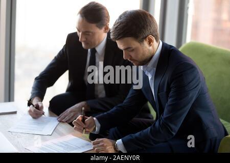 Empresarios exitosos en trajes firma contrato, acuerdo de asociación
