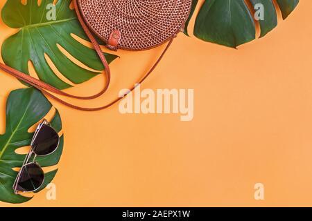 Bolsa rota de forma redonda y gafas de sol tumbado en una monstera hojas sobre fondo amarillo