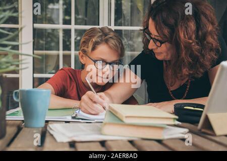 Joven estudiante haciendo los deberes en casa con libros de texto, periódicos y pad digital ayudado por su madre. Mum escrito sobre el copybook enseñar a su hijo.