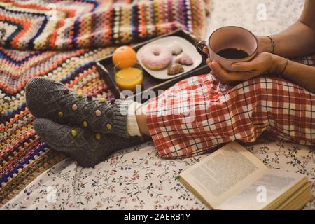 Mujer joven tumbado en la cama colorida desayunar en vacaciones. Mañana en una acogedora habitación caliente con jugo natural galletas de Navidad y donut.