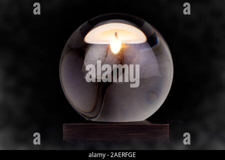 Una bola de cristal con una vela reflejada en ella contra un fondo ahumado negro.