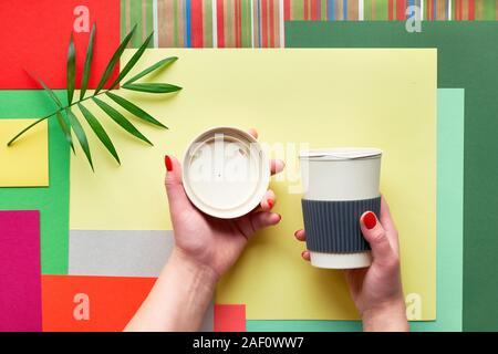 La taza de café de bambú (mantener la taza o taza de viaje) con tapa en manos femeninas en abstracto multicolor geométrica rectangular de fondo de papel con hojas de palmera. Creati