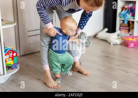 Poco lindo adorable rubia niño chico haciendo los primeros pasos con el apoyo de la madre en la sala de juegos en casa. Feliz divertido niño que aprende a caminar con la ayuda de mamá Foto de stock