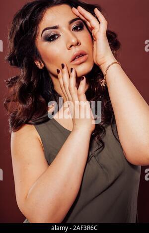 Hermosa chica peinado rizos en un fondo marrón