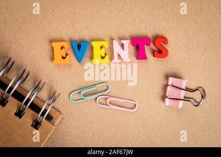 Los acontecimientos. Texto de letras coloridas de madera sobre fondo de cartón