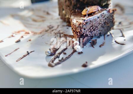Detalle de una tarta de chocolate con salsa de chocolate, en una placa blanca, el cual está decorado con pequeñas bolas de plata. Cierre con antecedentes muy suave en b