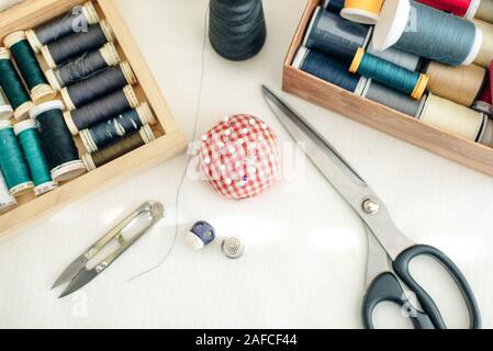Composición laicos plana con tijeras y Suministros de coser sobre fondo blanco.