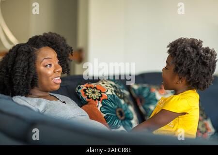 Madre afroamericana jugando y hablando con su hija.