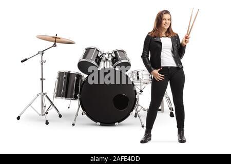 Longitud total retrato de una joven posando con un conjunto de tambor y baquetas holding aislado sobre fondo blanco.