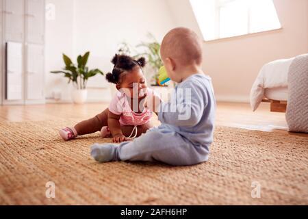 Baby Boy y Girl jugar con juguetes en una alfombra en casa juntos