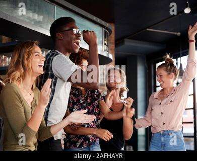 Grupo de Amigos masculinos y femeninos celebrando mientras estás viendo en la pantalla de juego en el bar de deportes