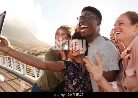 Sonriente joven amigos posando para Selfie en pasarela exterior juntos