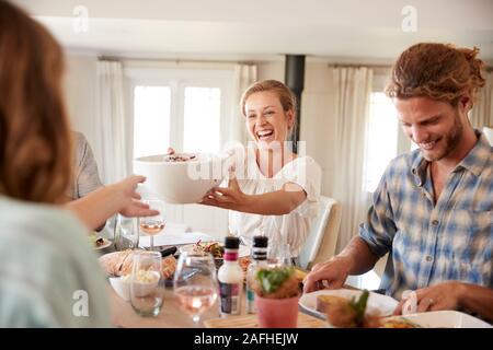 Jóvenes amigos adultos pasando a través de los alimentos durante el almuerzo en la mesa de la cena, cerrar