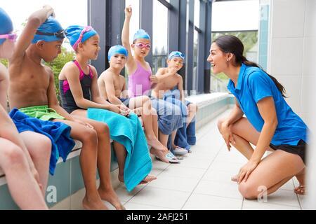 Entrenador femenino que dan a los niños en clases de natación información mientras se sientan en el borde de la Piscina cubierta
