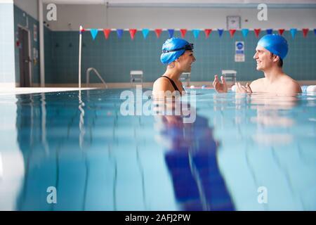 Profesor de natación masculina mujer dando lecciones Uno a uno en la piscina