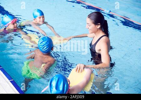Entrenador femenino en agua, dando grupo de niños Lección de Natación en Piscina cubierta