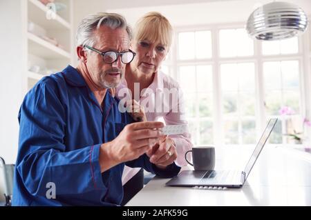 Pareja madura con el hombre en silla de ruedas buscando información sobre medicamentos en línea usando el portátil