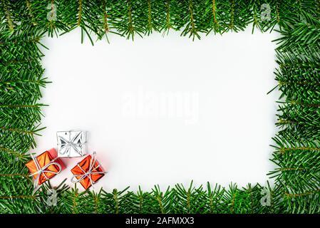 Marco de ramas de abeto, en la esquina inferior izquierda tres regalos envueltos, aislado en un fondo blanco.