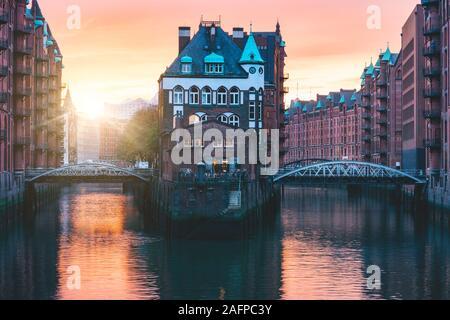 Puerto Viejo de la ciudad de Hamburgo, Alemania, Europa. Famoso distrito histórico almacén con agua palacio castillo al atardecer luz dorada