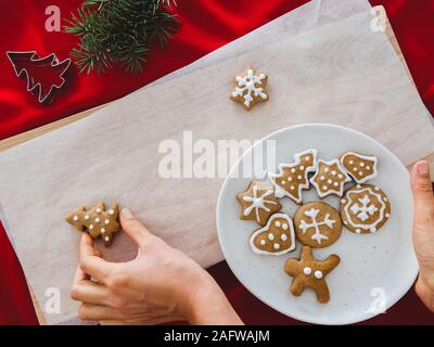 Galletas caseras en forma de árbol en la placa y mano sujetando galletas de Navidad de diferentes formas: estrella, abeto, navidad, sobre fondo de madera blanca, plana