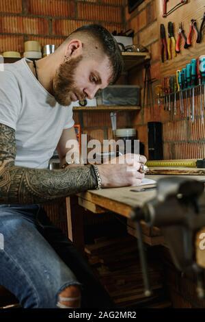 Artesano artista haciendo un nuevo diseñador de producto de madera en su casa taller.