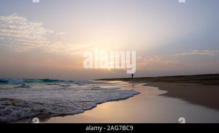 Una persona que disfruta de un paseo nocturno en una apartada playa tropical en Cabo Verde al atardecer