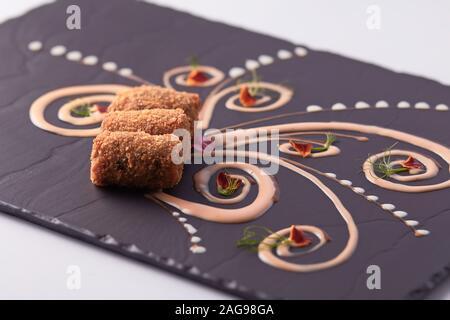 Primer plano de deliciosos dedos de pescado en un hermoso decorado pizarra negra
