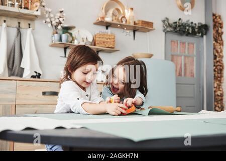 Infancia feliz. Dos niños juegan con juguetes de color amarillo y naranja en la cocina blanca
