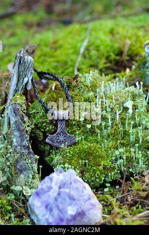 Un martillo de Thor amuleto de plata sobre un tocón cubiertas de musgo