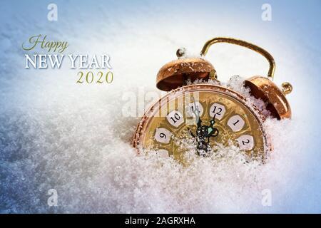 Feliz Año Nuevo 2020 texto y un reloj despertador vintage en la nieve muestra cinco minutos antes de las doce, el concepto de espacio con copia de tarjeta de felicitación