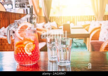 Jarra con jugo de naranja y dos tazas vacías de pie en una tabla en un café caliente, en un día soleado. Espacio para copiar texto.