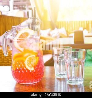 Jarra con jugo de naranja y dos tazas vacías de pie en una tabla en un café en un caluroso día de verano.