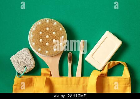 Concepto de residuo cero y el cuidado del medio ambiente. Eco friendly Bolsas textiles, jabón, cepillo de dientes, jabón de bambú accesorios sobre un fondo verde. Vista superior