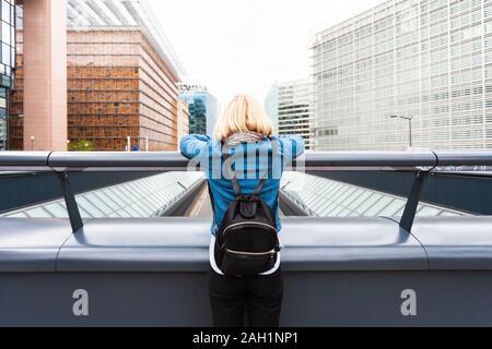 Una mujer se levanta sobre un puente con su espalda a la cámara, con el telón de fondo de una moderna oficina trimestre, Bélgica