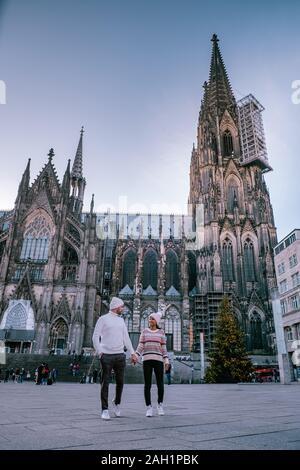 Pareja joven visitar el mercado de Navidad en Colonia, Alemania, durante un viaje de la ciudad, el hombre y la mujer en el mercado de Navidad