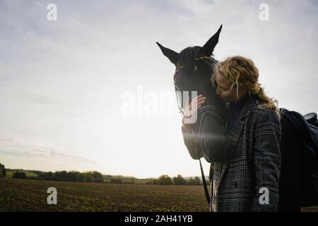 Afectuoso joven con caballo en un campo en el campo al atardecer Foto de stock