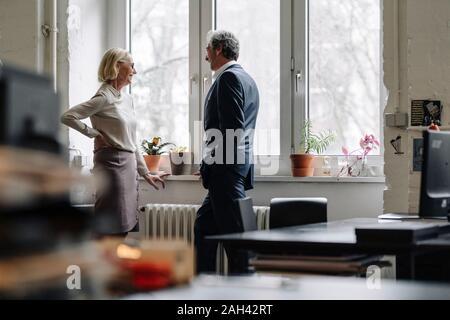 Empresario sonriente y empresaria hablando en la ventana de la oficina