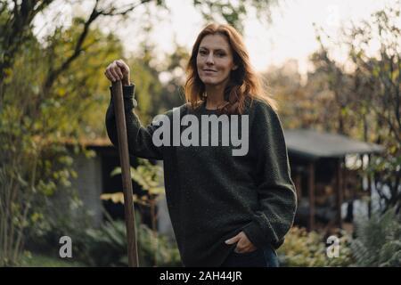 Mujer trabajando en su jardín, sosteniendo la pala