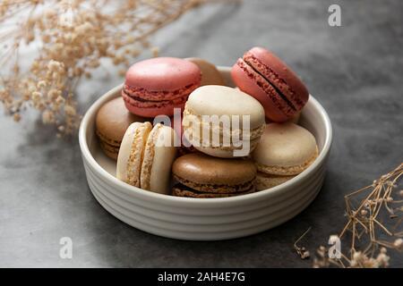 Francés macaron tartas en una placa de cerca. Crema, marrón, rosado, macarons con espacio de copia.