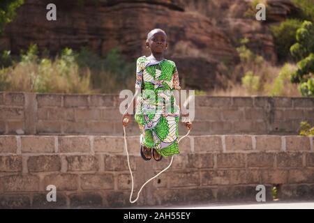 Pequeña muchacha africana con un hermoso vestido verde concentrándose en su omitiendo el rendimiento