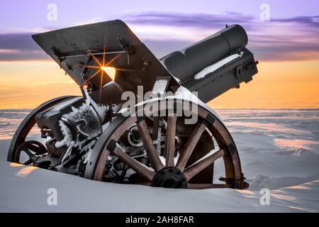 Cerca de un cañón de la primera Guerra Mundial en un monumento conmemorativo de la cima de la montaña cubierto de nieve al amanecer