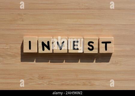 Invertir en madera 3d las letras del abecedario sobre un fondo de madera de bambú