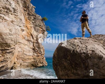 Viajero con mochila en las rocas cerca del mar en busca de distancia. Los viajes de vacaciones de verano. Apuesto joven turista caucásica hombre en ropa casual al aire libre