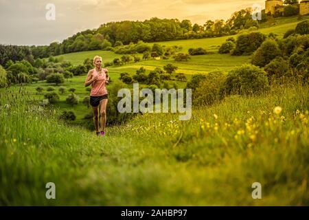 Una mujer de mediana edad se ejecuta a través de las colinas