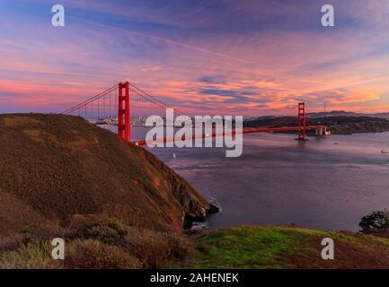 Panorama del puente Golden Gate al atardecer con el Marin en primer plano, el horizonte de San Francisco y las nubes de colores en el fondo