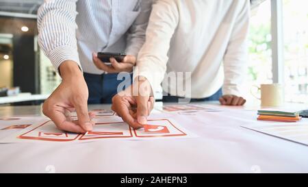 Desarrollador de aplicaciones de interfaz de usuario Ux diseñar con papel modelo en preparar la aplicación móvil, primer plano.
