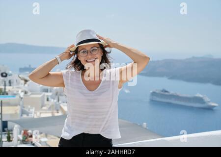 Retrato de mujer de mediana edad viajando en crucero de lujo en el Mediterráneo. Mujer sonriente mirando a la cámara en la isla de Santorini, espacio de copia