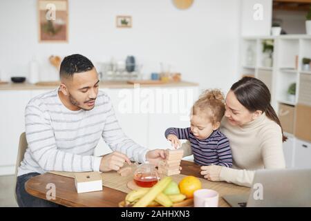 Retrato de familia de raza mixta feliz jugando con poco lindo hija mientras disfruta del desayuno en casa, espacio de copia