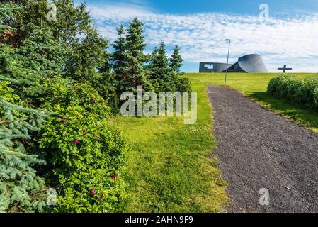 El paseo a la iglesia en Blonduos Blonduoskirkja aldea del noroeste de Islandia. Árboles y flores del parque está en primer plano.