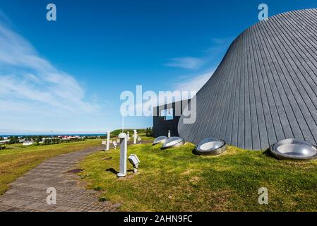 Parte de la iglesia en Blonduos Blonduoskirkja aldea del noroeste de Islandia. La aldea de edificios y cielo azul están en segundo plano.